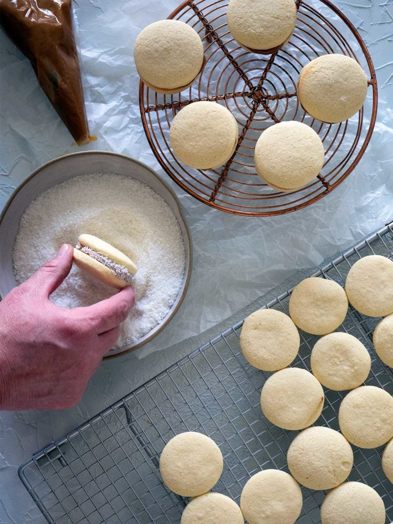 short bread biscuits on racks and a person rolling alfajores de maicena in coconut