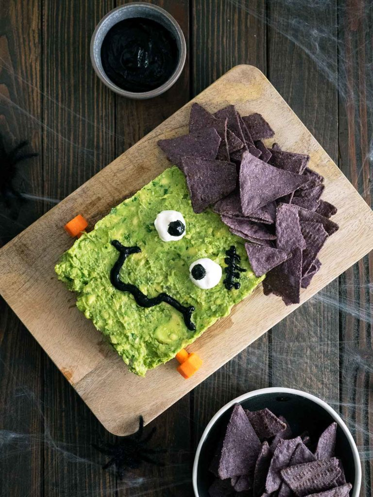 guacamole decorated to look like frankenstein on a wooden board