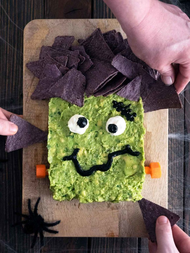 hands digging in with purple corn chips to the plated guacamole