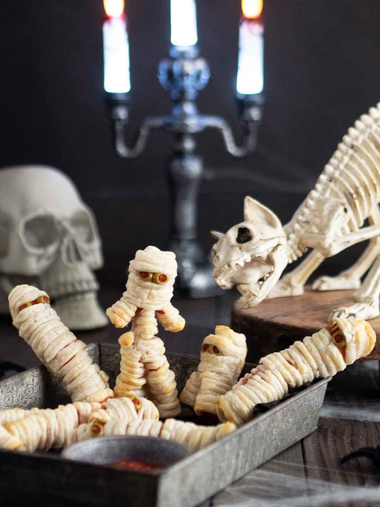 mummy hot dogs in a metal containers with a skeleton cat and skull in the back ground