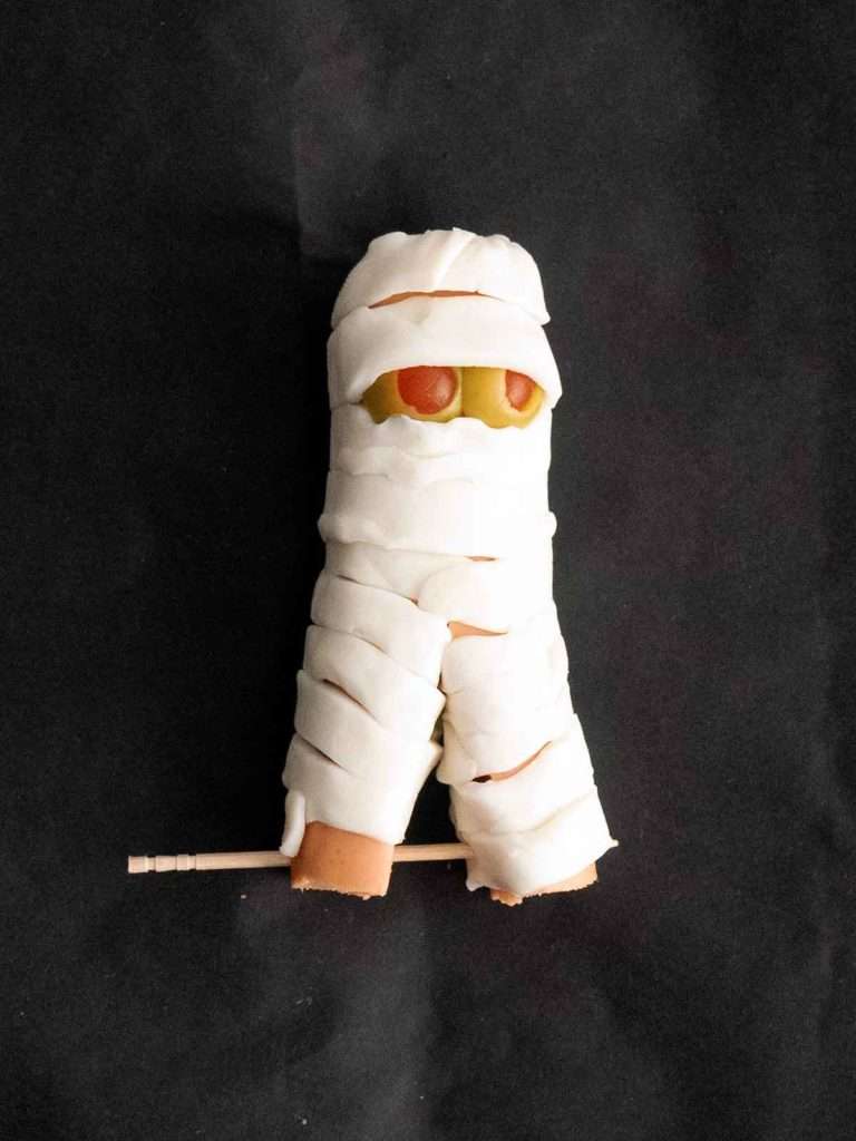 mini hot dog mummy with legs secured by toothpicks
