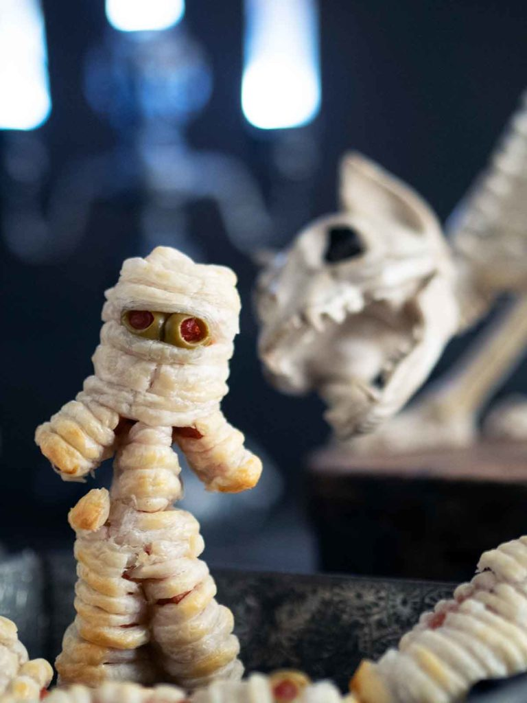 hot dog mummy with arms and legs and cat skeleton in the background