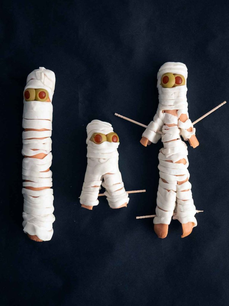 hot dogs wrapped up like mummies on black paper with toothpicks securing arms and legs