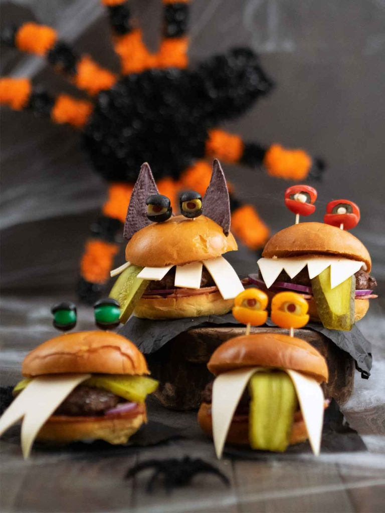 four monster burgers grouped together with a big black and orange spider in the background