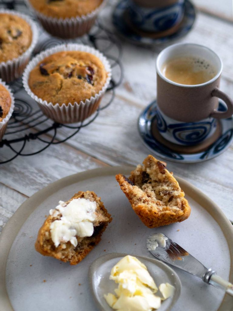 muffin split open on a plate spread with butter, cup of coffee and tray with muffins in the background