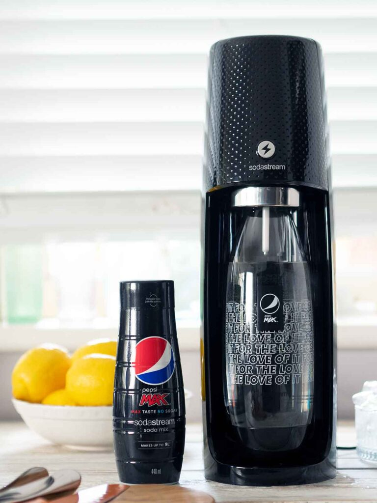 sodastream machine on counter with a bottle of pepsi max syrup next to it
