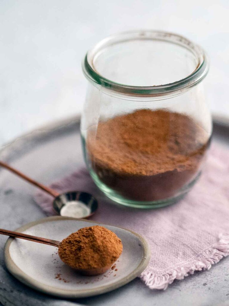 spice mix in a glass jar with some on a spoon on a shallow plate