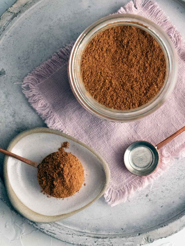 pumpkin spice mix on a spoon and in a glass jar on a pink piece of cloth on a plate