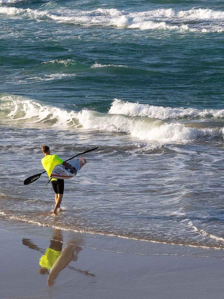 man taking kayak into the surf