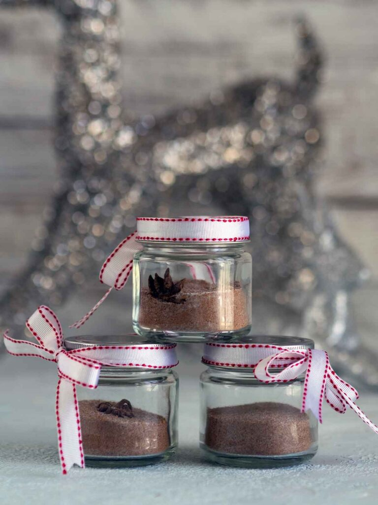 Jars of Christmas sugar stacked on top of each other with ribbon.