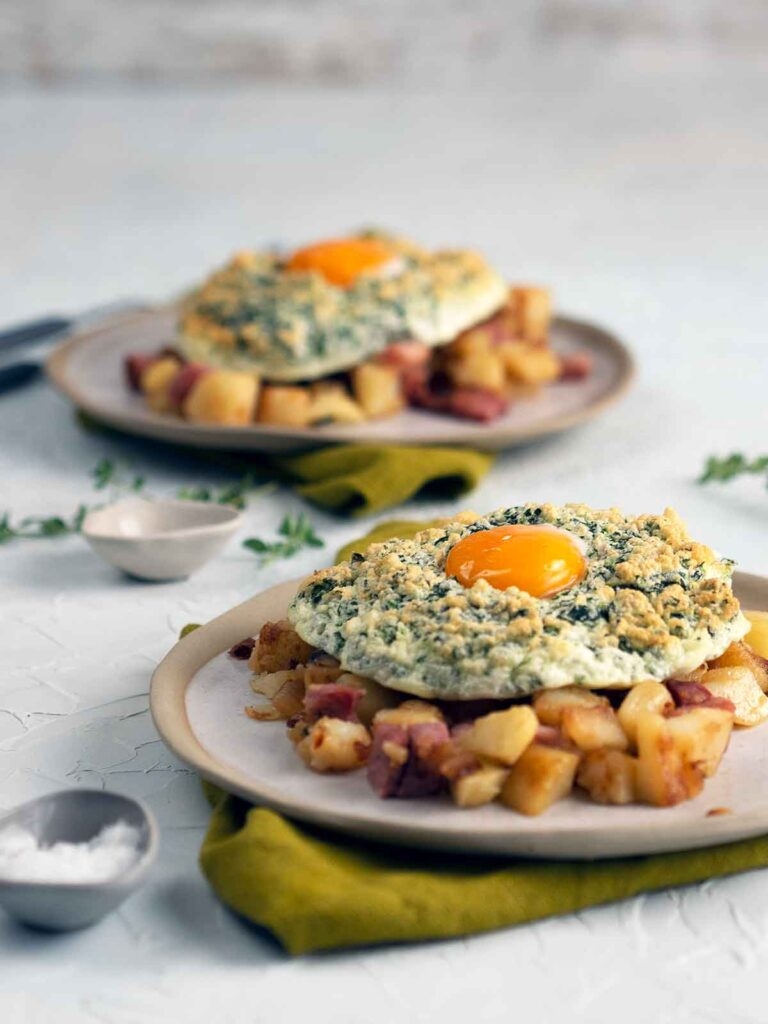 green eggs on top of ham hash on two plates