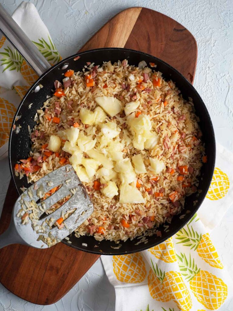 adding pineapple to the fry pan
