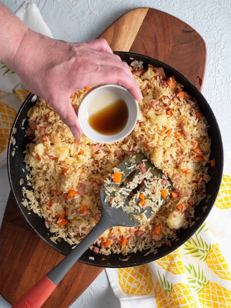 adding sesame oil to the ingredients in the fry pan