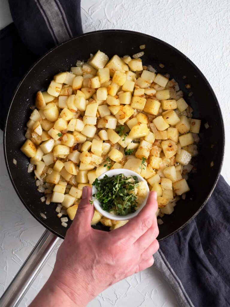 a person adding thyme to the recipe