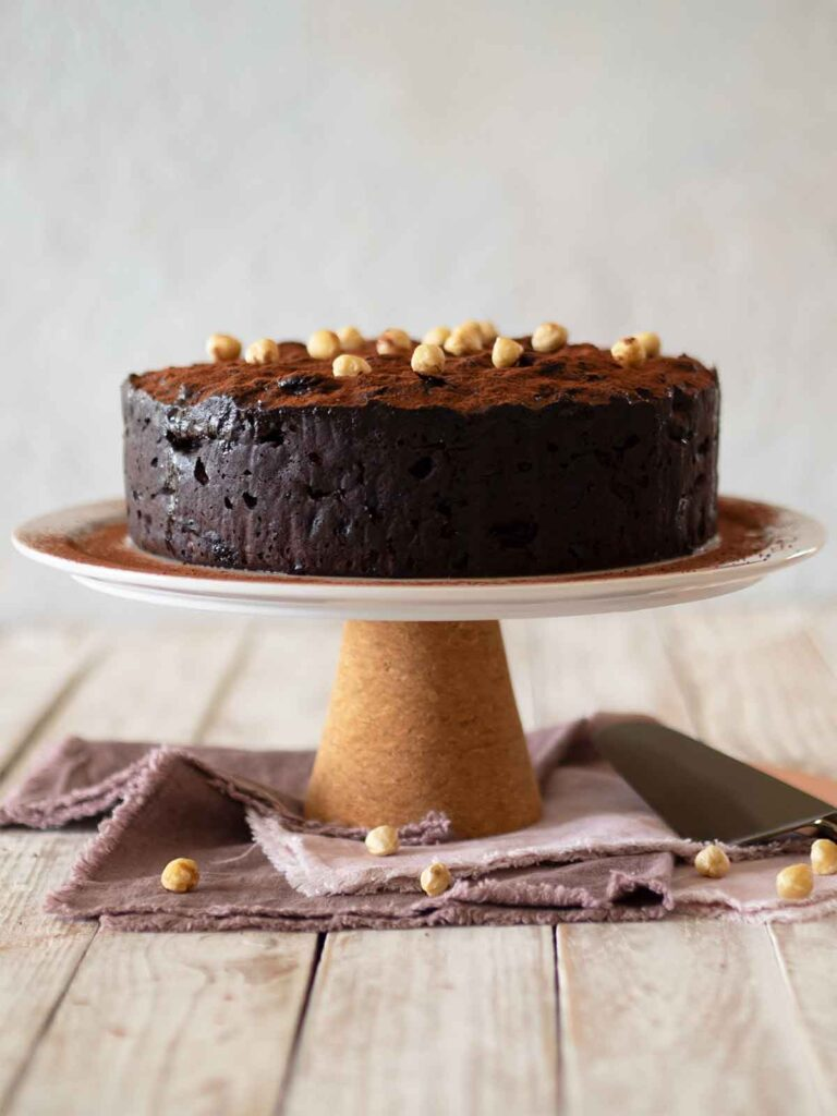 cake on a cake stand decorated with cocoa powder and roasted hazelnuts