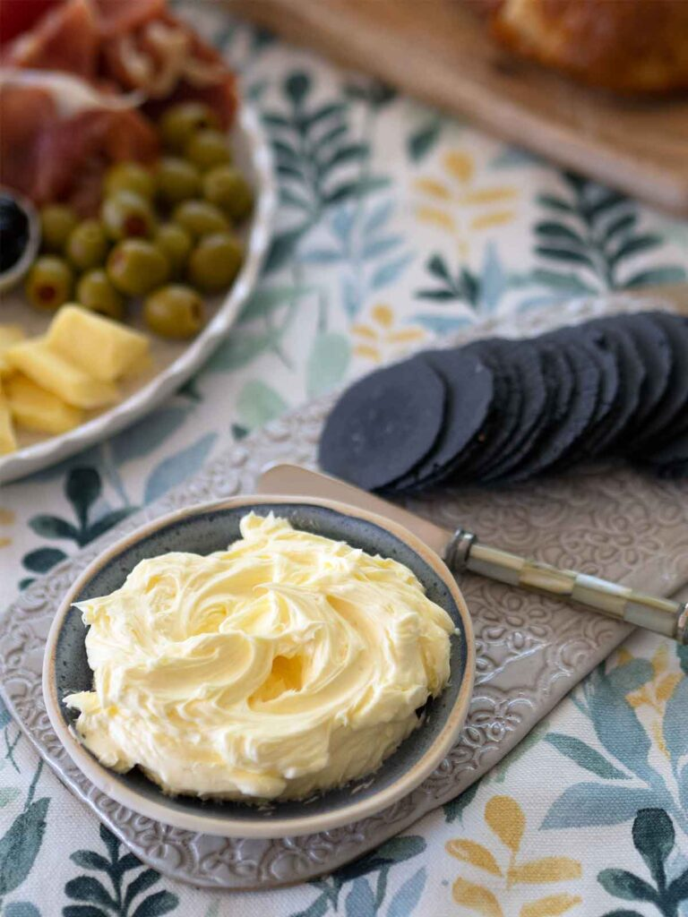 butter on table in a small dish with crackers and antipasto