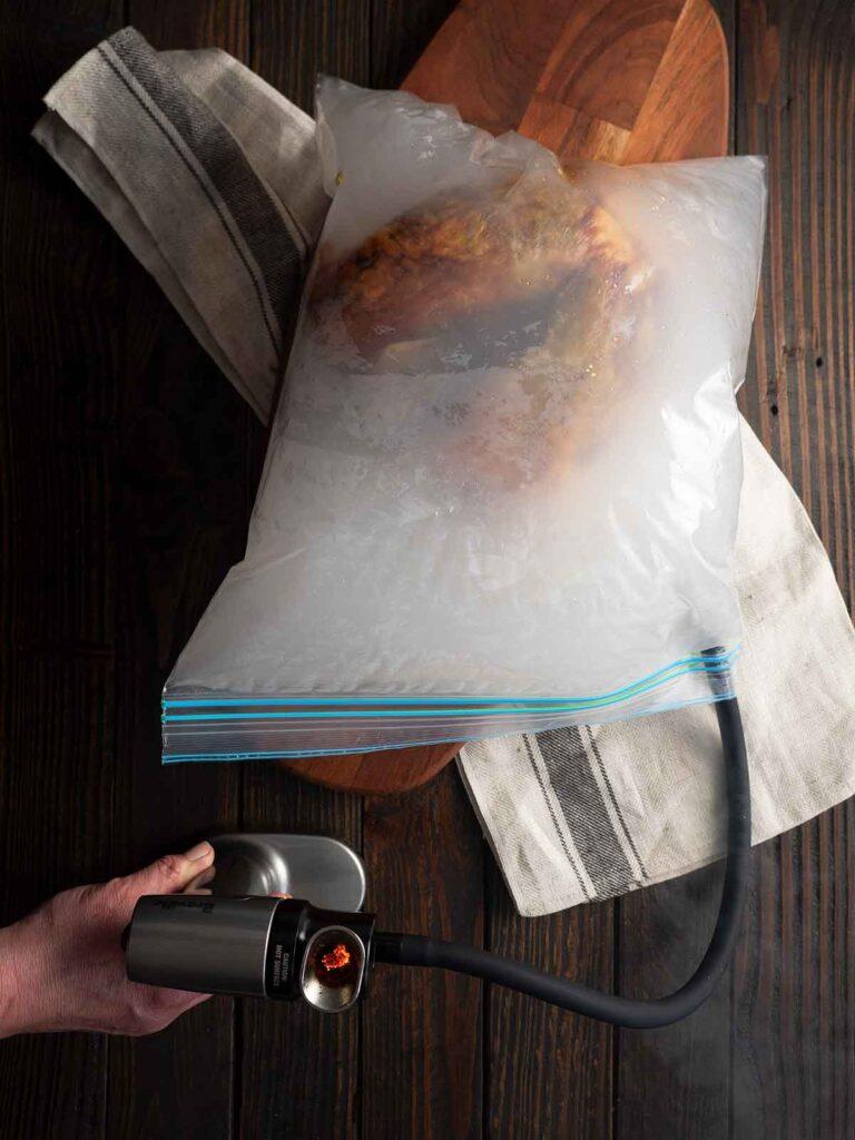 smoking gun adding smoke to the zip lock bag that holds the turkey