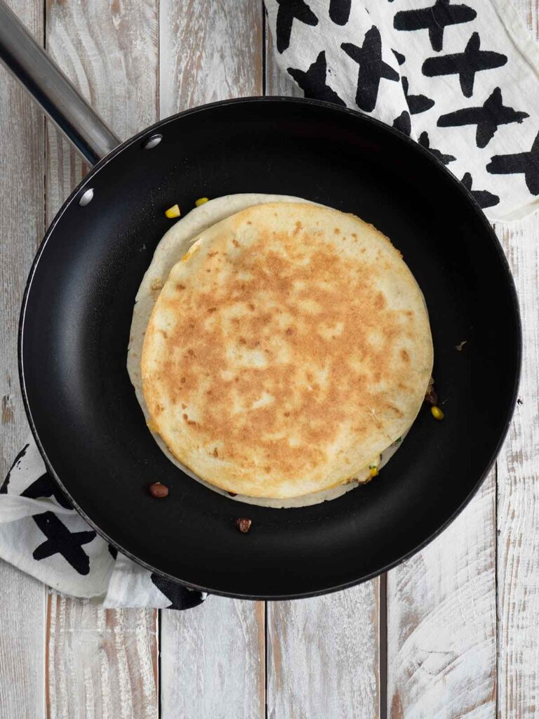 flipping quesadillas over in a fry pan