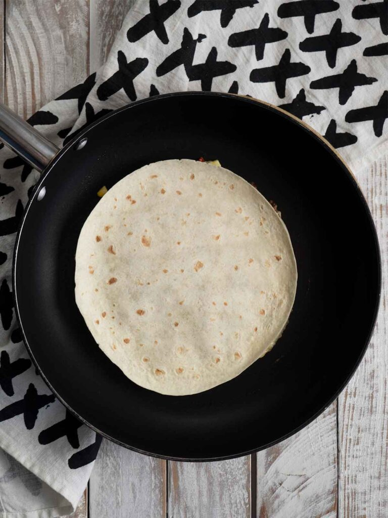 cooking quesadillas in a fry pan