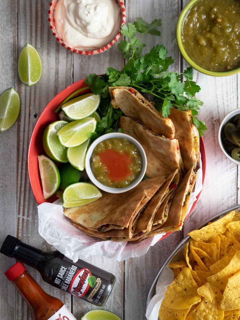 turkey quesadillas in a bowl with sauce and limes also on the table is sour cream, salsa, hot sauce and corn chips