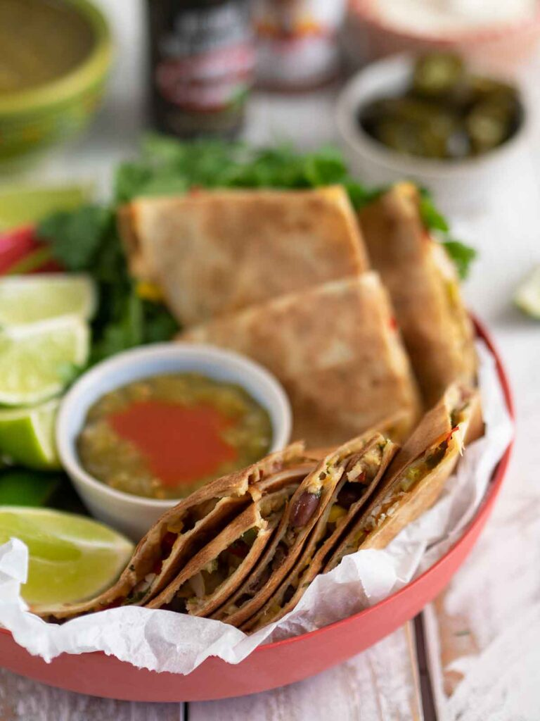 turkey quesadillas in a dish with sauce and lime