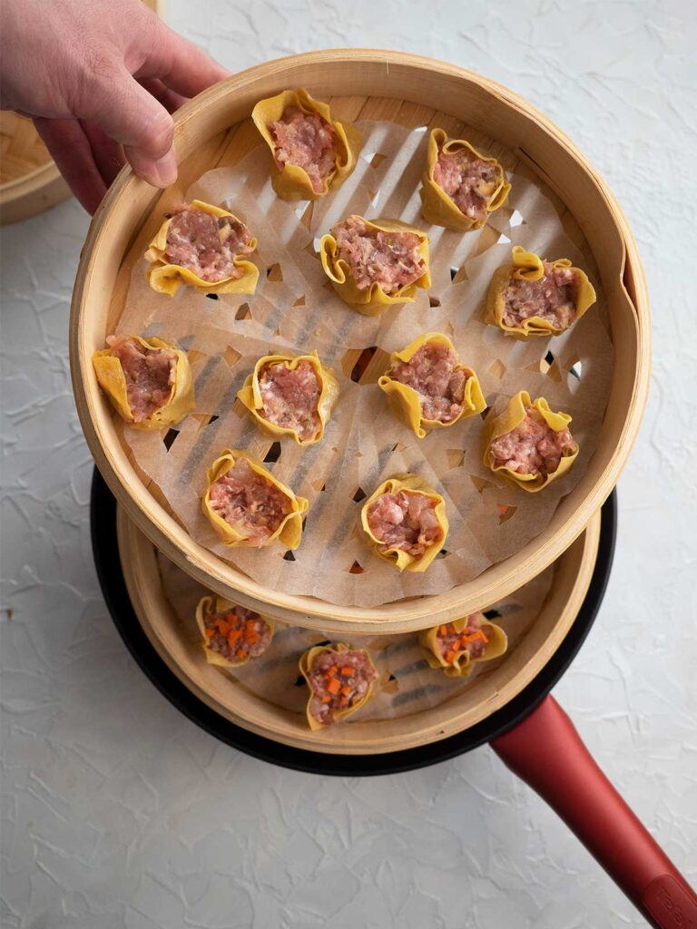 a person stacking another basket with dumplings on top of basket already sitting in wok