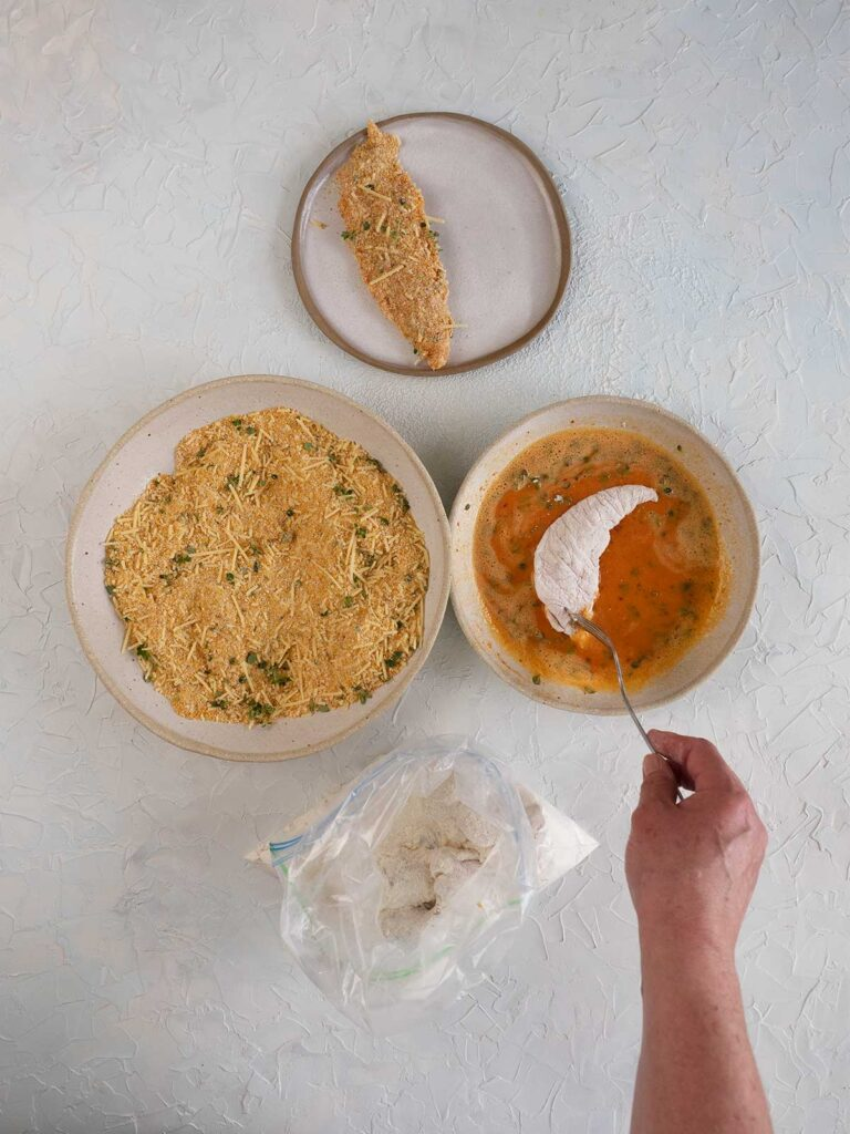 placing flour coated chicken in egg mixture