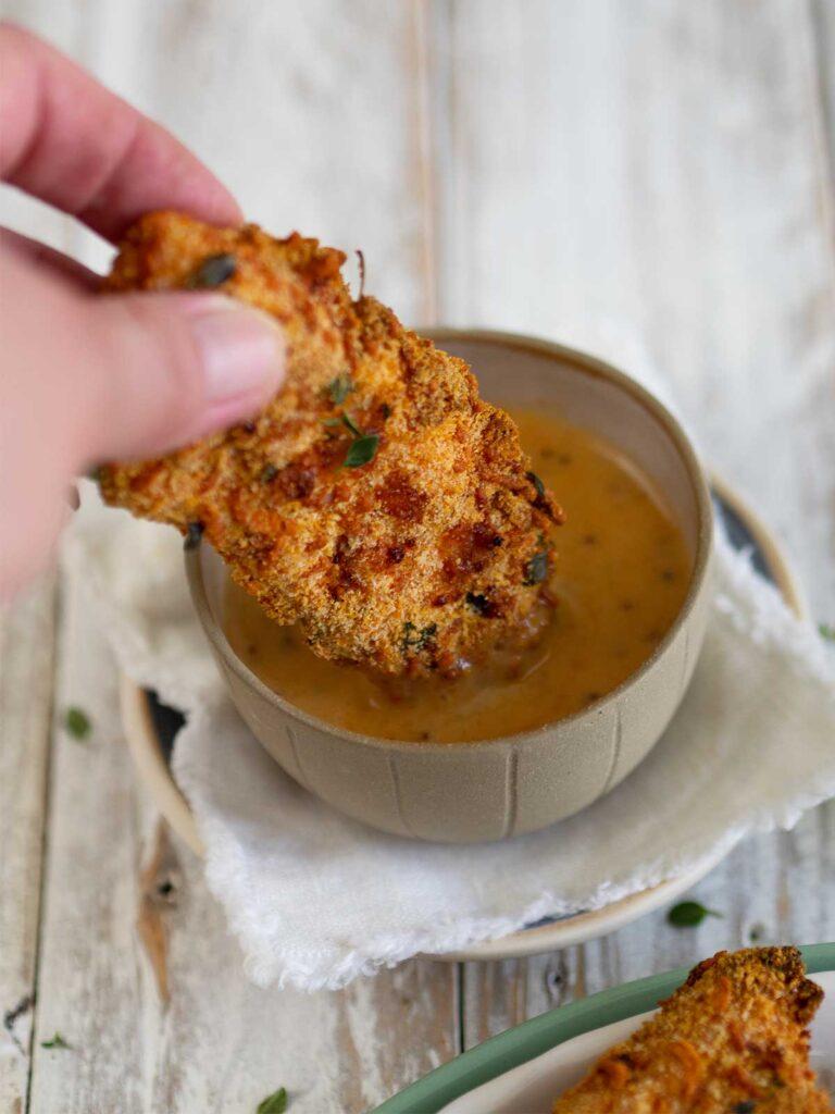 dipping an air fryer chicken tender in honey mustard sauce