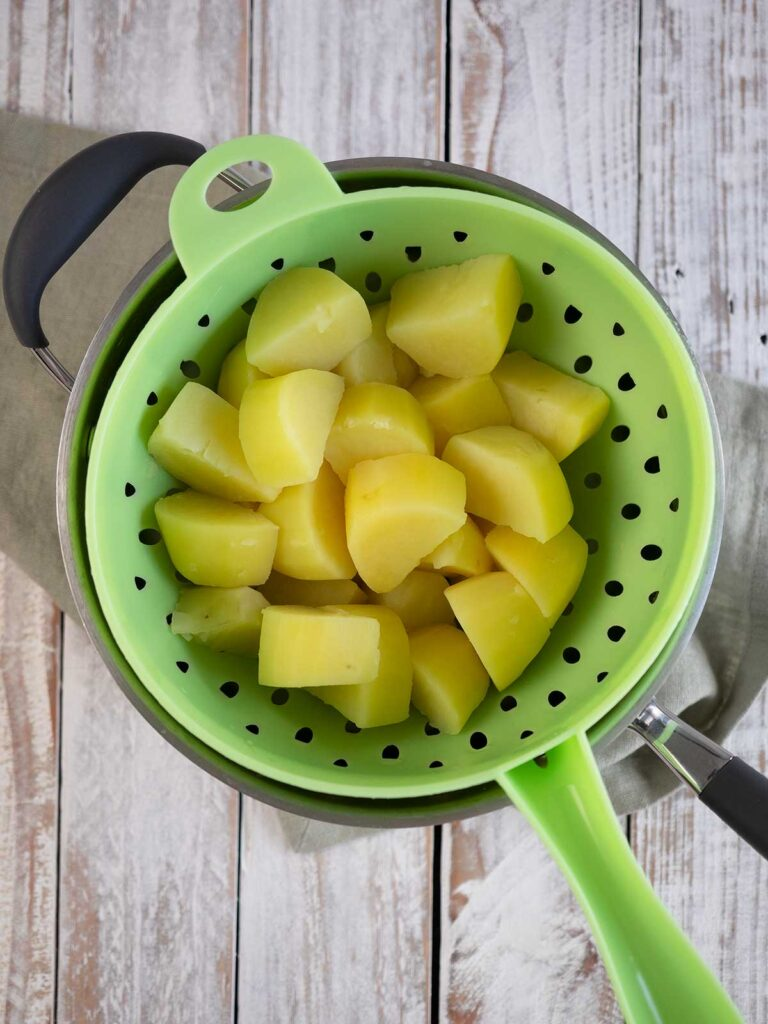 boiled potatoes in a green drainer sittintg on the po