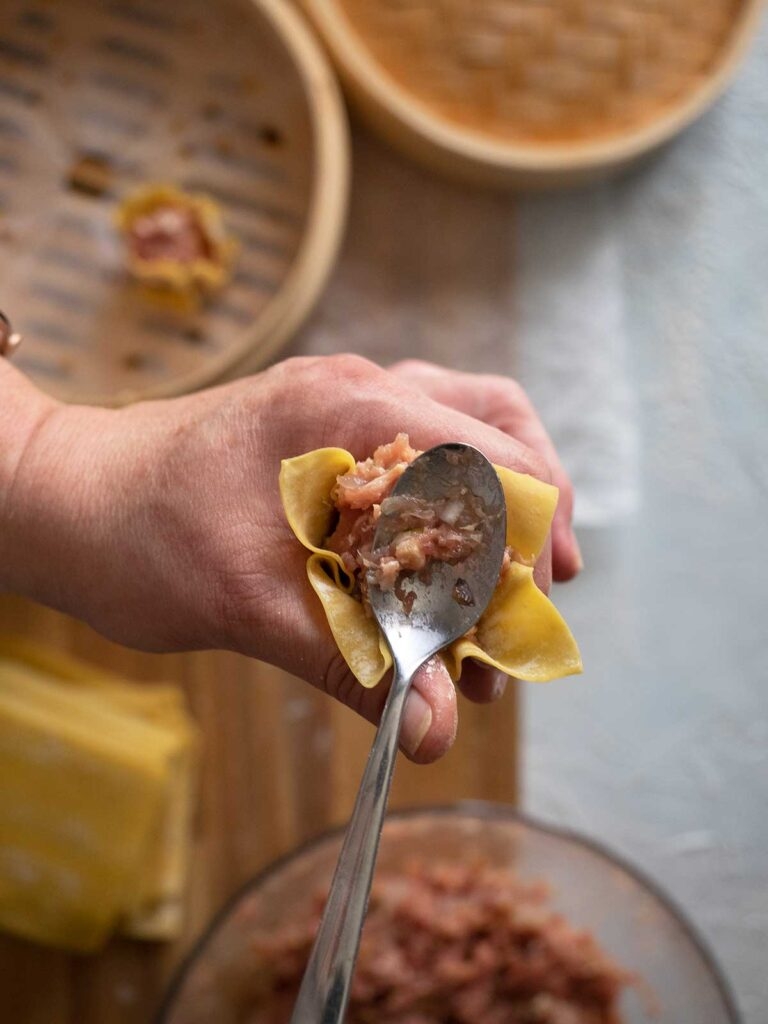 wonton wrapper being wrapped around dumpling stuffing and being smoothed down by a teaspoon