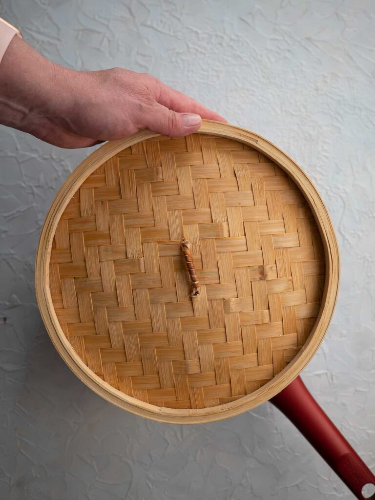 bamboo steamer basket lid being placed on top of the steamer baskets