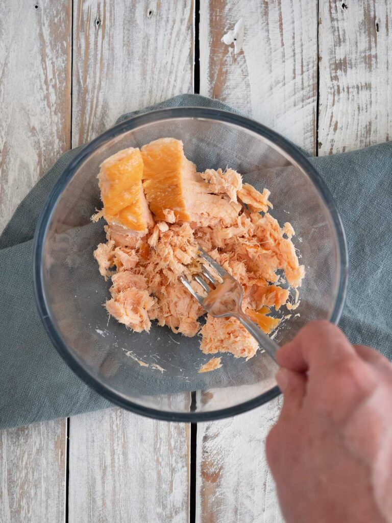 mashing hot smoked salmon in a glass bowl