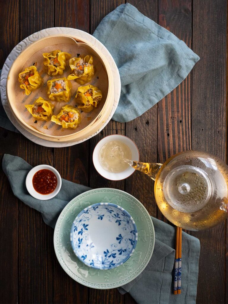 table setting with siu mai in basket and tea being poured