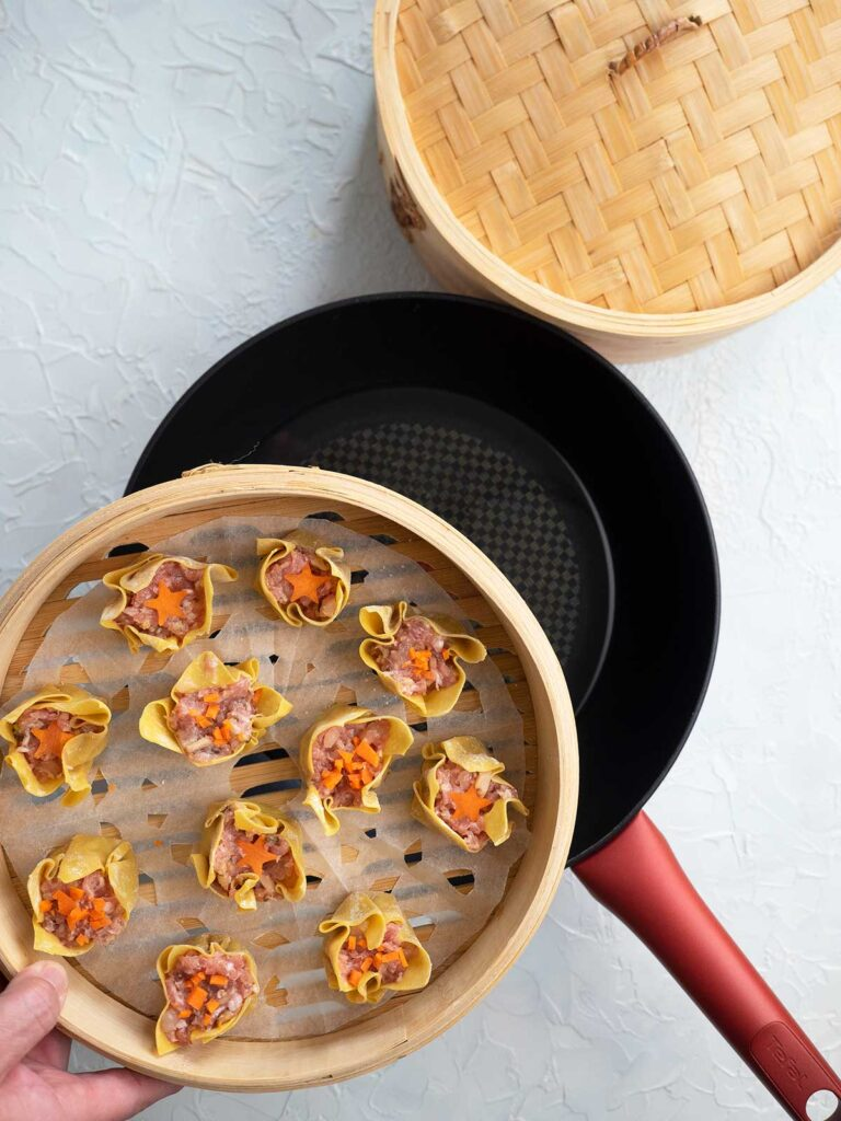 siu mai (shumai) in a steamer basket being placed of wok with water