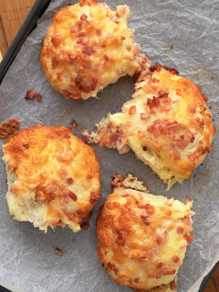 cheese and bacon rolls on a baking sheet