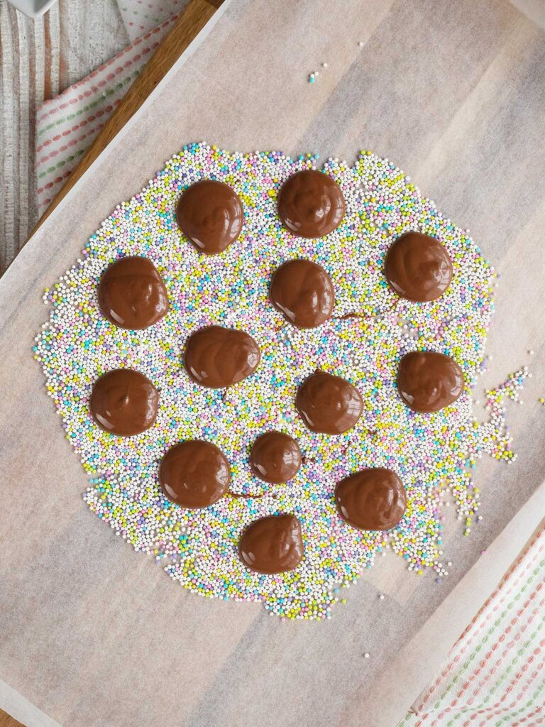 sprinkles on a surface with piped chocolate rounds on top