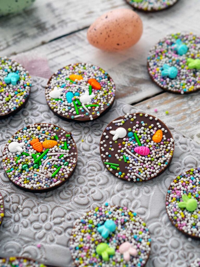 choclate discs with sprinkles on a ceramic tray with Easter egg