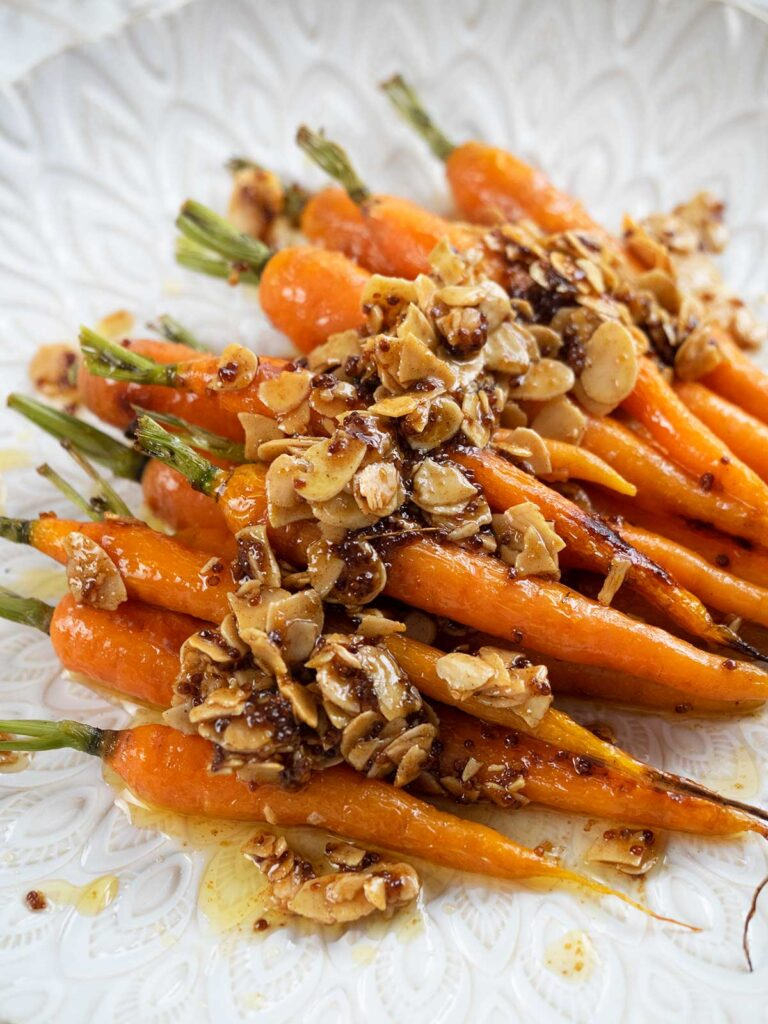 roasted dutch  carrots with almonds on a white platter