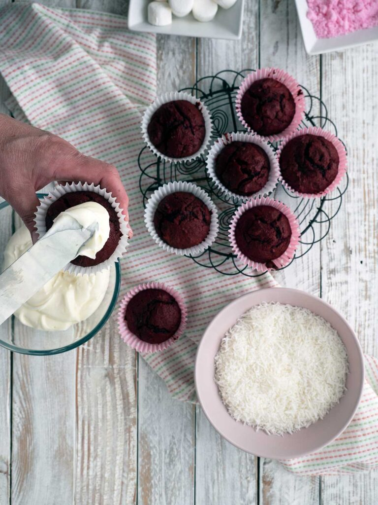 frosting the top of a red velvet cupcake