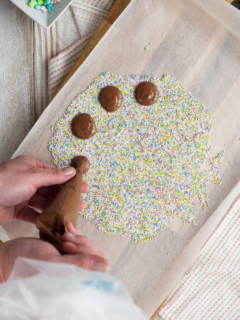 piping chocolate rounds on a layer of nonpareils