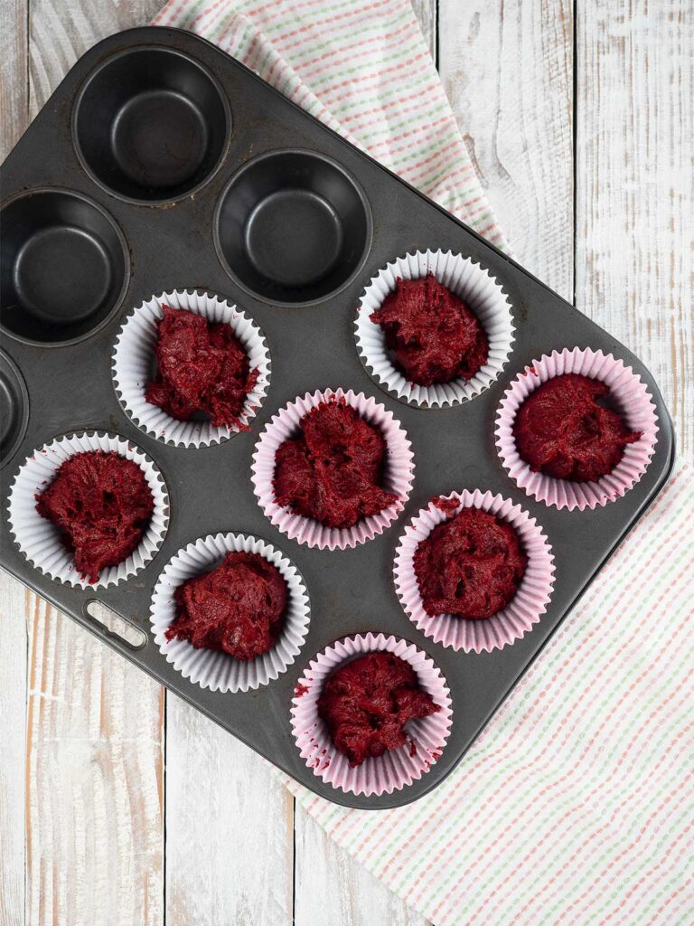 red velvet cupcake mixture in paper cases in tin