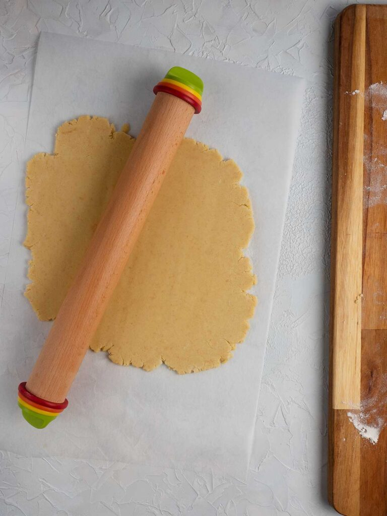 dough being rolled out by a wooden rolling pin