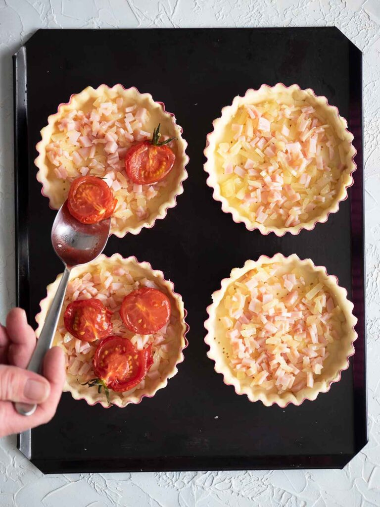 placing tomatoes in tart shells