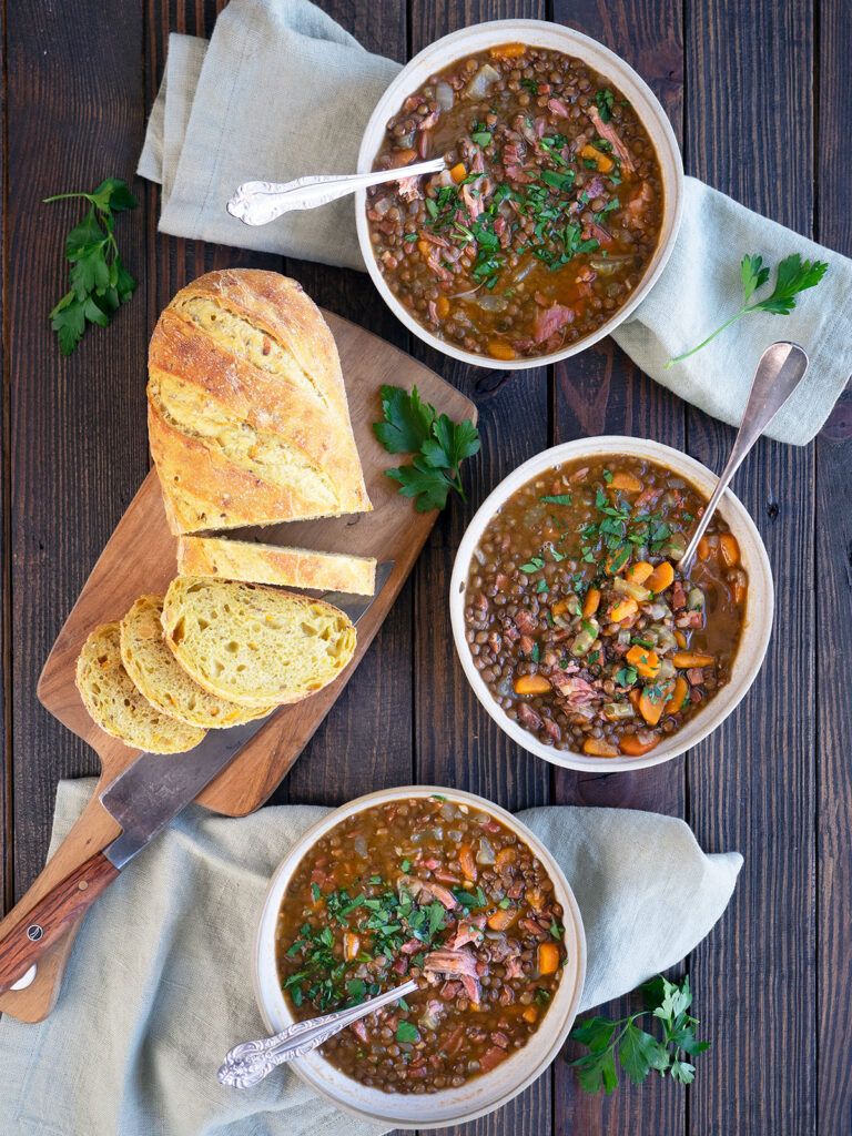 three bowls of soup with a loaf of bread on a cutting board