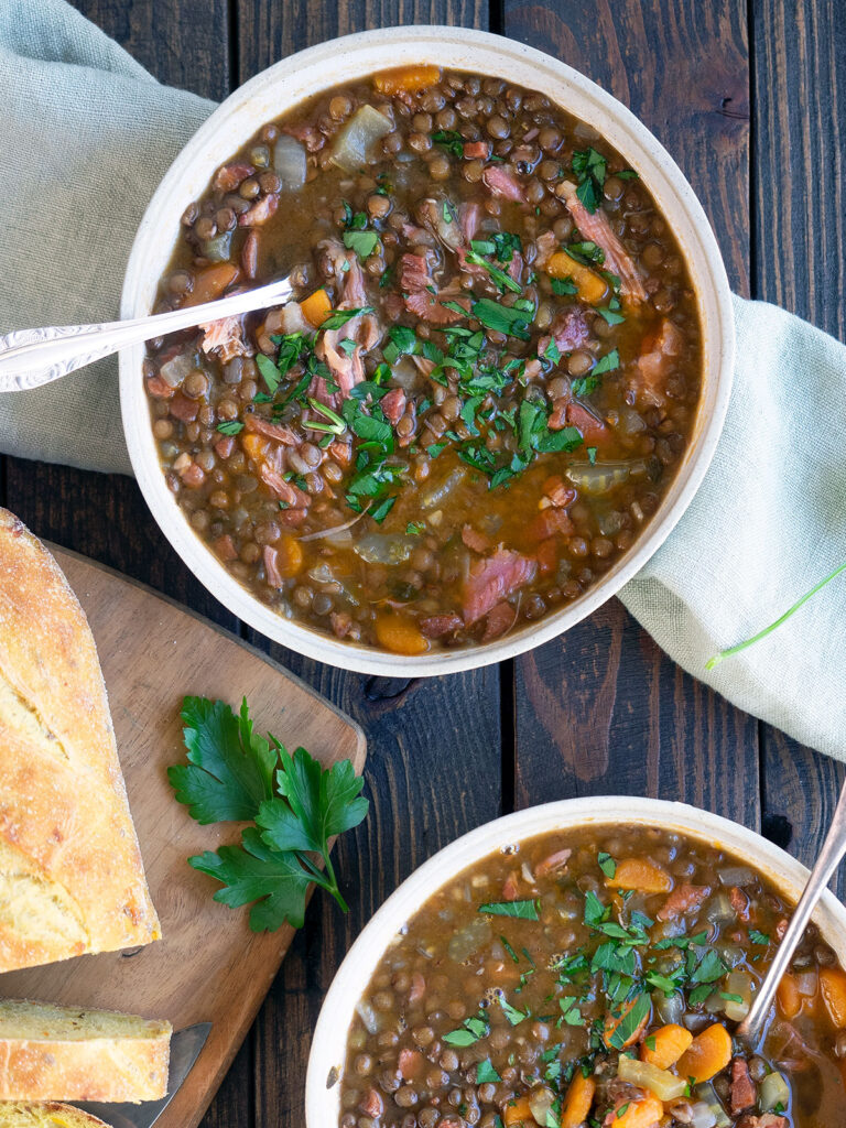ham and lentil soup in bowls with spoons