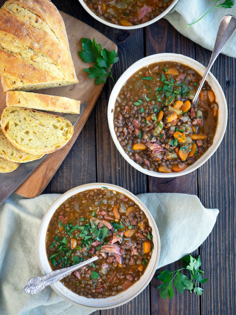 ham and lentil soup in bowls with bread on a cutting board