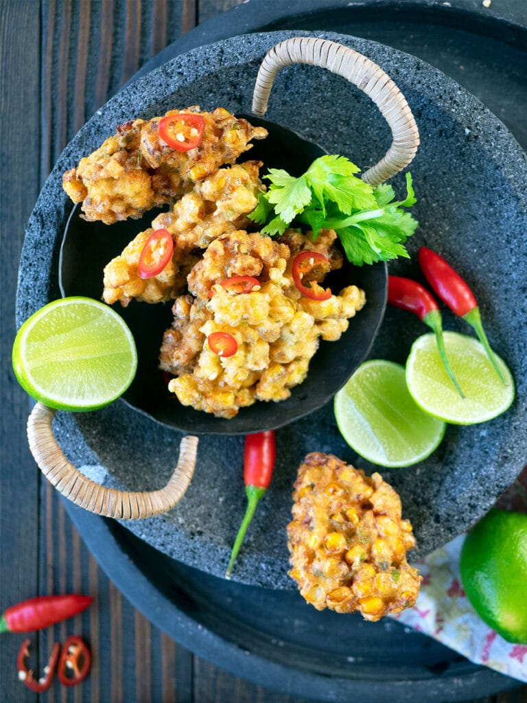 Cooked corn fritters in a serving bowl with limes