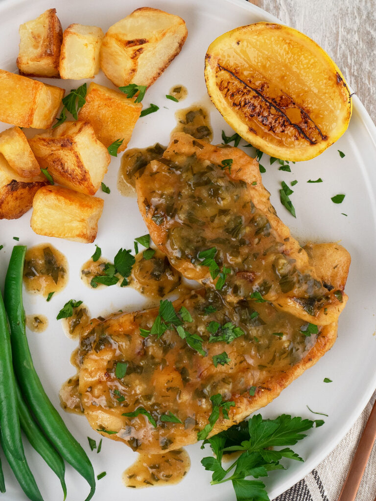 chicken in lemon sauce on a white place with potatoes, beans and a lemon cheek