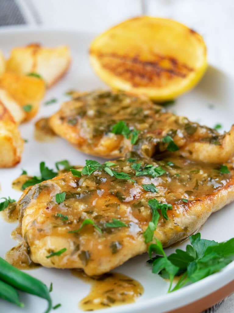 chicken in lemon sauce on a white plate with a lemon cheek