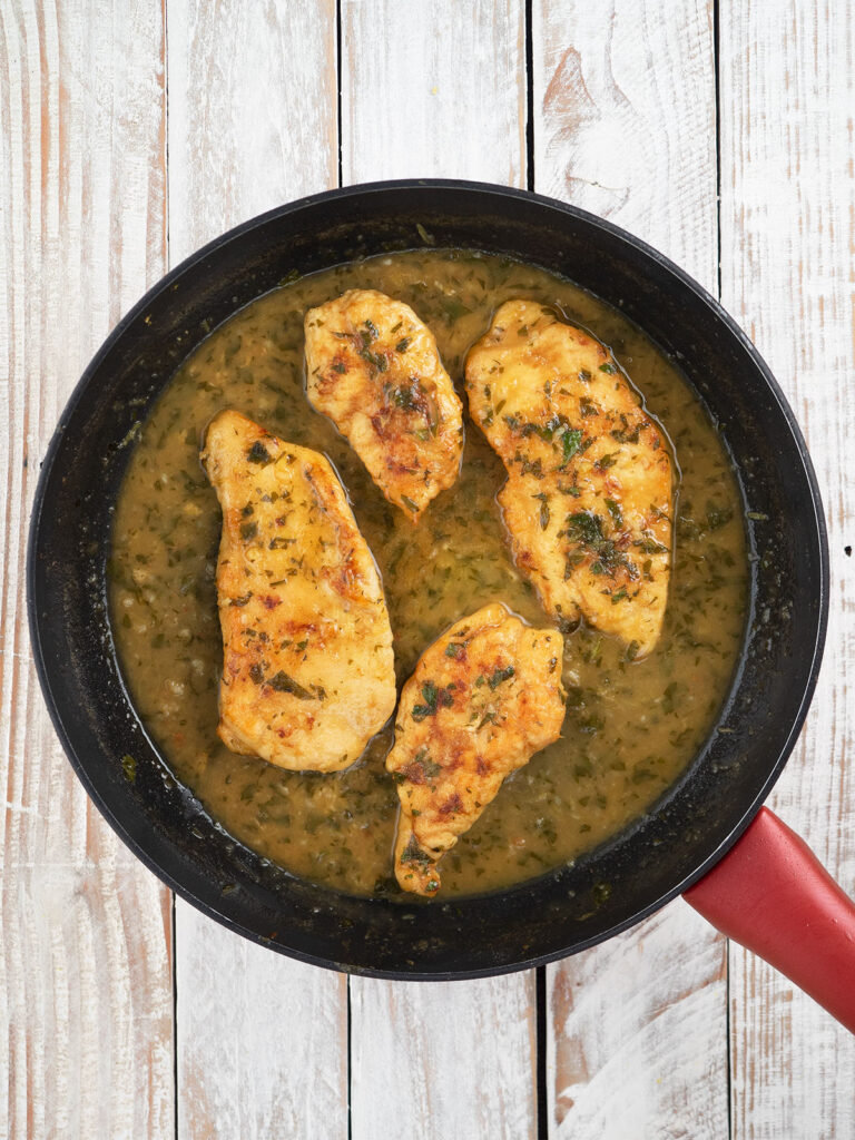 chicken fillets in pan with sauce coated